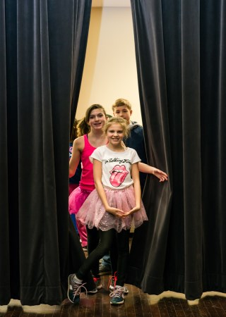 Children coming out from behind curtain