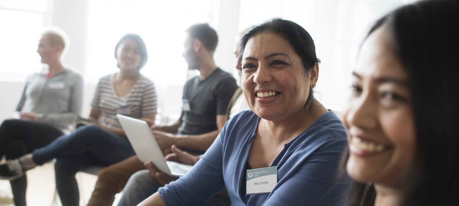 woman smiling at a community meeting